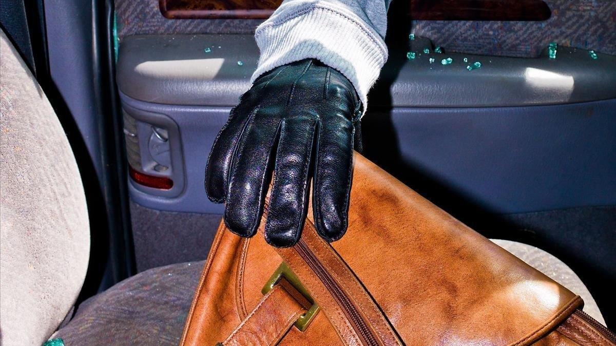 Un ladrón sustrae un bolso de un asiento.