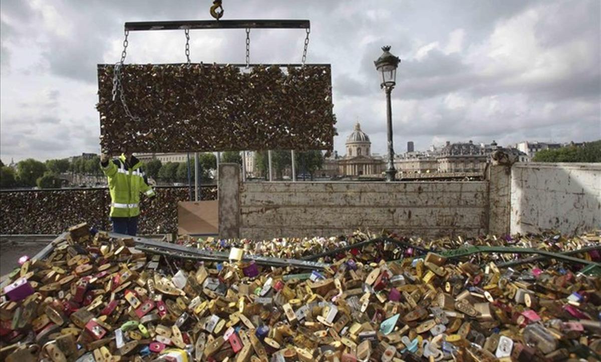 Unos operarios depositan en un camión una de las barandillas del puente de las Artes, en París, abarrotada de candados.