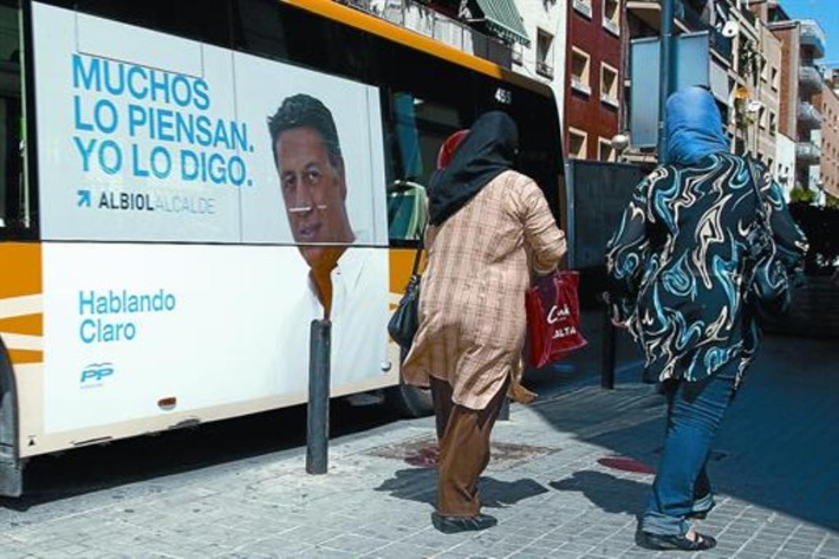 Dos inmigrantes pasan junto a un autobús con una pancarta de campaña de Albiol en el barrio de la Salut de Badalona, el pasado 18 de mayo.
