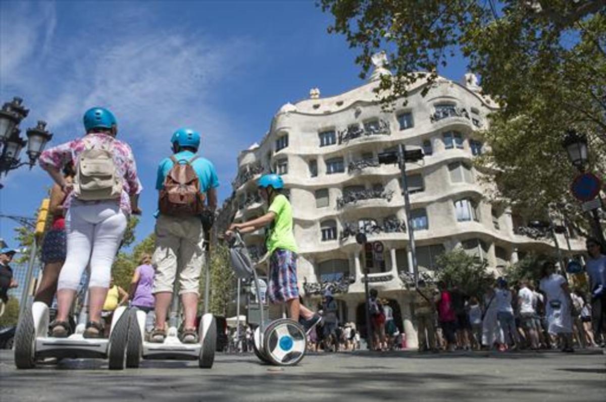 Turistas sobre 'segways' frente a La Pedrera, en Barcelona.