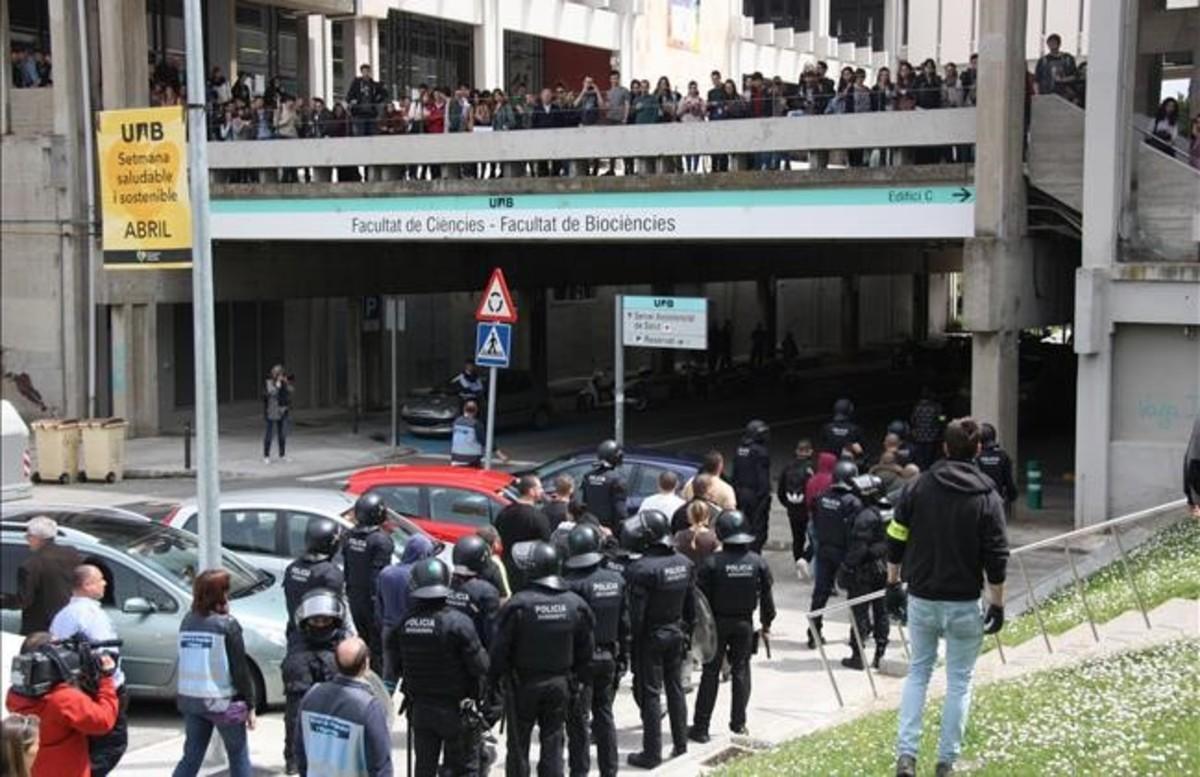 Los Mossos d'Esquadra escoltan al grupo de neonazis mientras estudiantes de la UAB les increpan.