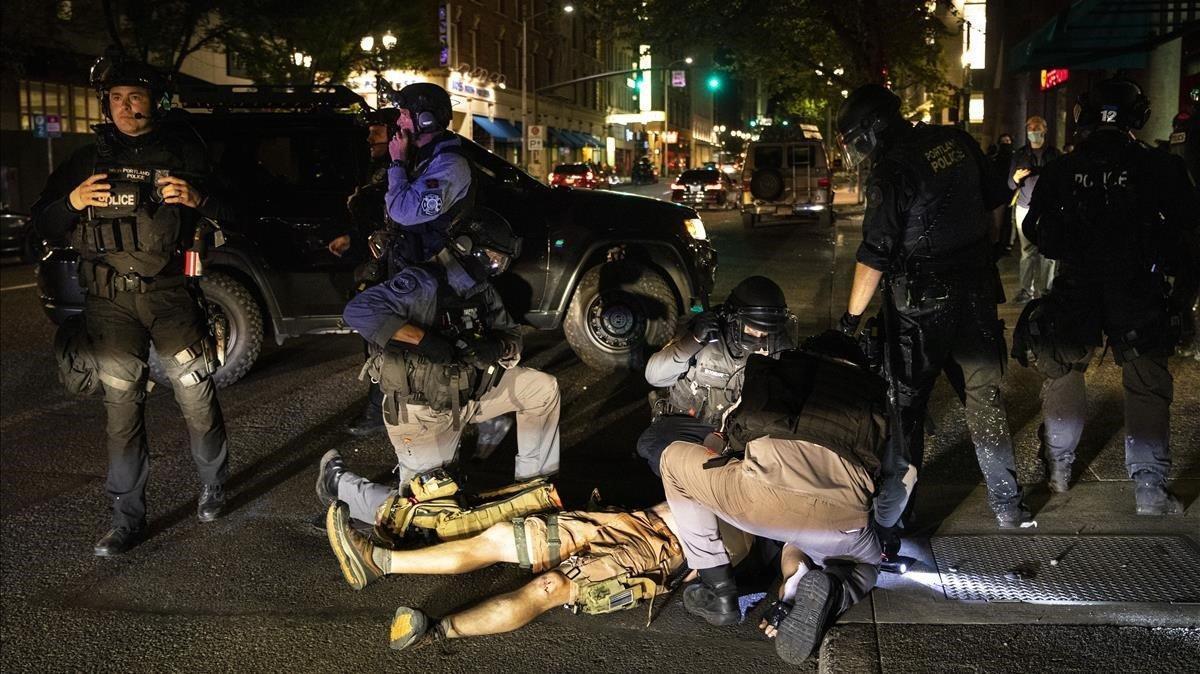 El cuerpo del hombre fallecido por disparos el sábado en Portland yace en el suelo rodeado de policías.