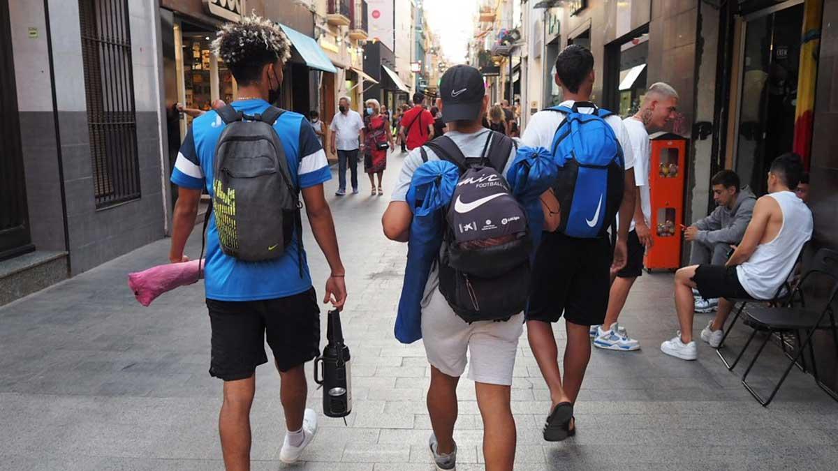 Tres jóvenes pasean por la calle del Mar de Badalona al volver de la playa.