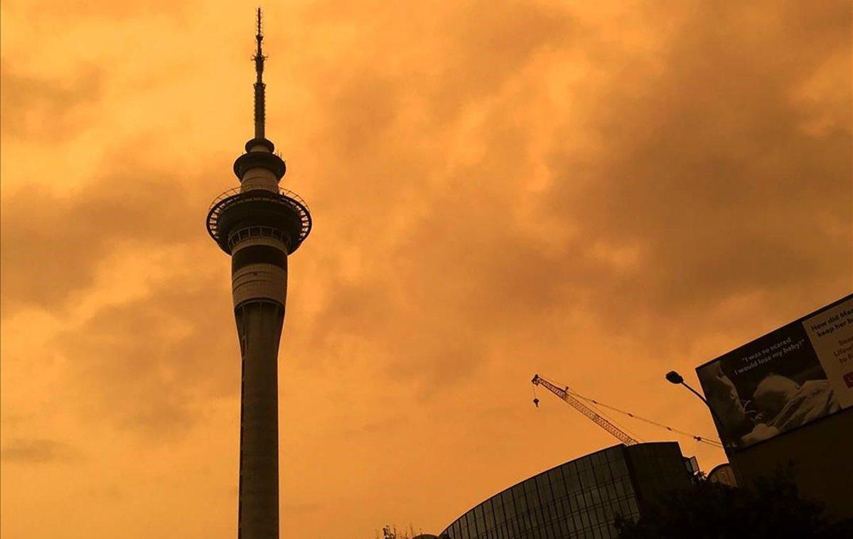 La silueta de la Sky Tower en Auckland (Nueva Zelanda) recortada contra un cielo naranja.