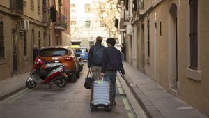 Turistas con maletas por las calles de la Barceloneta.