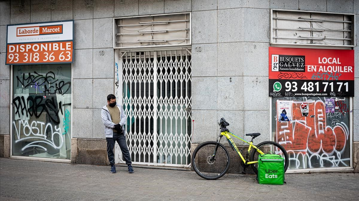 Un repartidor de comida delante de un establecimiento cerrado, en Barcelona.