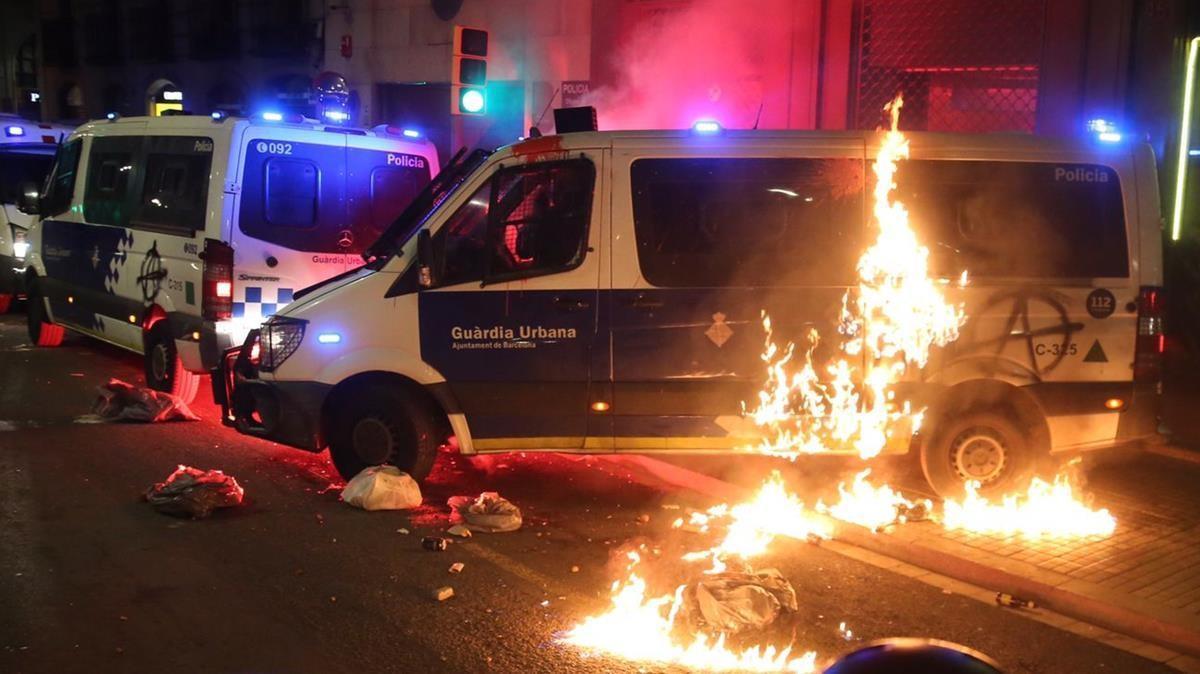 Un grupo de manifestantes prende fuego a una furgoneta de la Guardia Urbana, este sábado en las Rambles