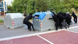 Unos jóvenes montan una barricada con contenedores en los accesos de la UAB, en Bellaterra, durante la jornada de huelga del 12 de mayo.