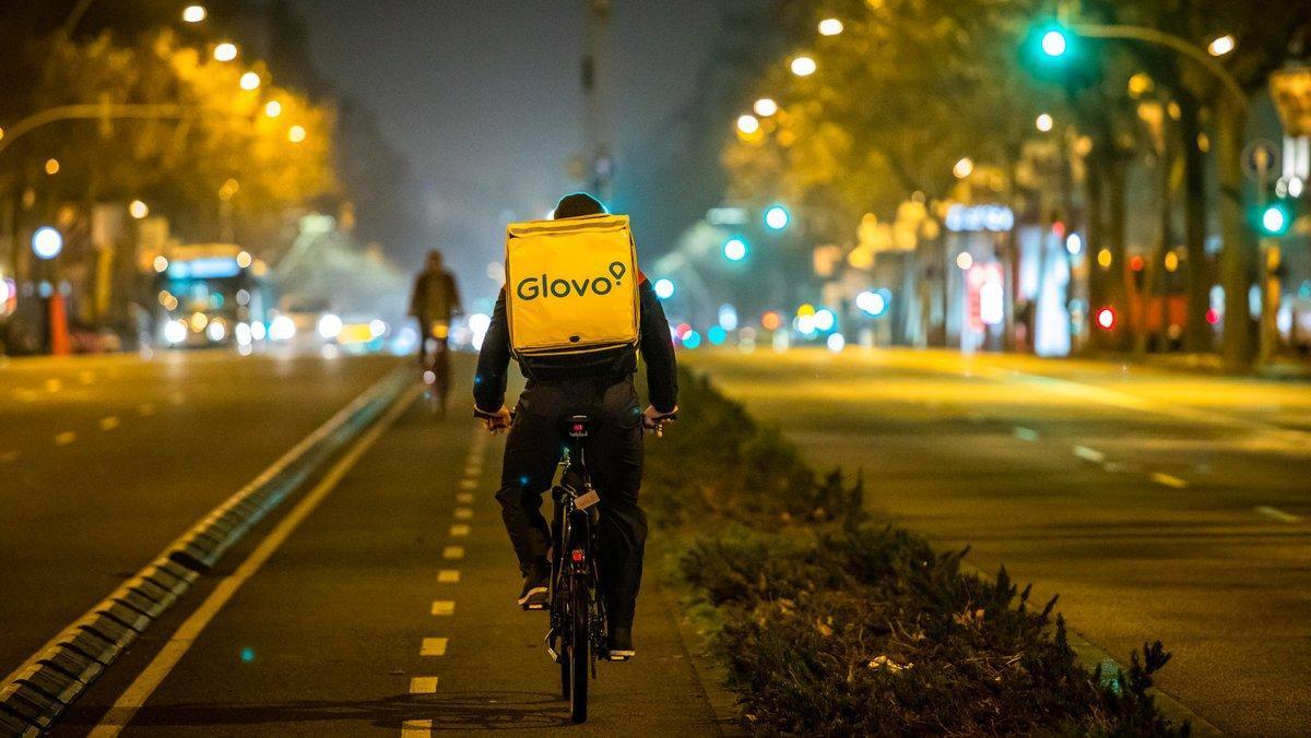 Repartidor de Glovo, mientras reparte de noche por la ciudad de Barcelona.