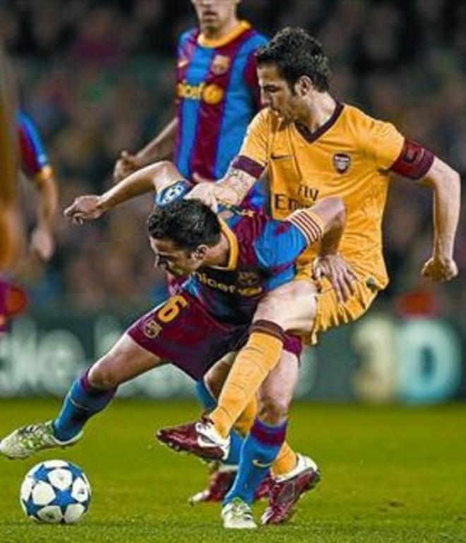 Cesc intenta arrebatar un balón a Xavi, anoche en el Camp Nou.