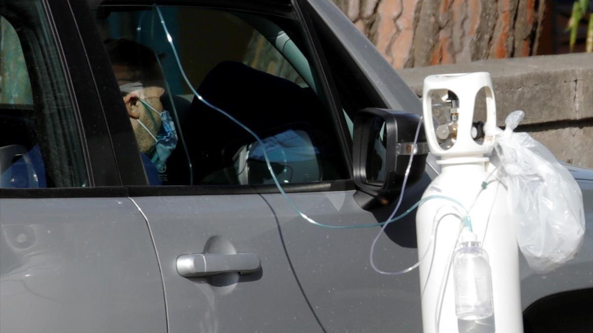 Un paciente recibe oxígeno en su coche mientras espera a ser atendido en Nápoles.