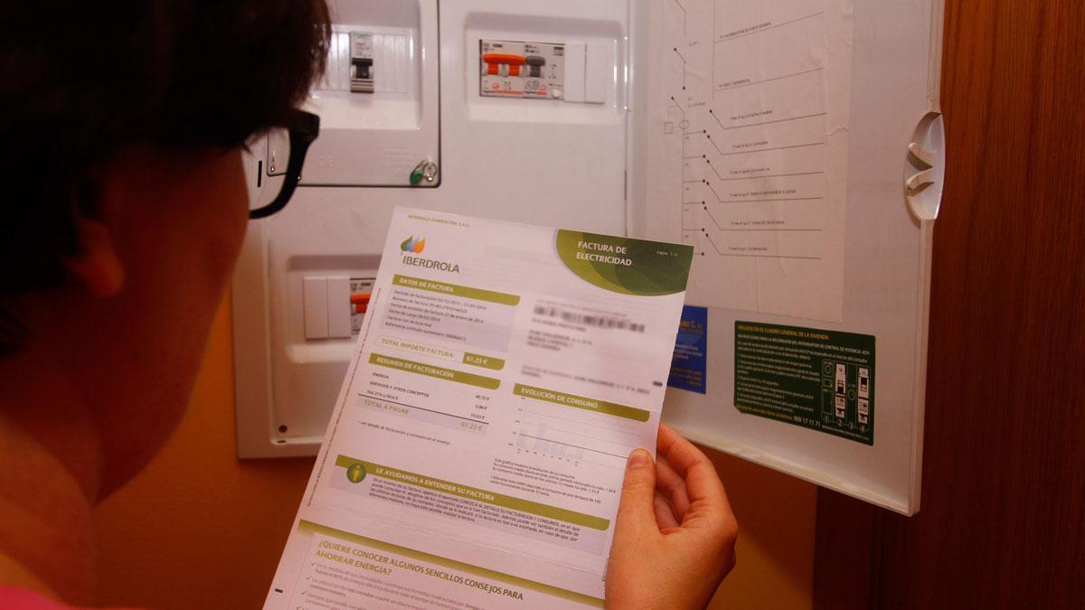 Factura de la luz. ¿En qué cambia con la nueva reforma?. En la foto, una mujer consulta una factura de la electricidad.