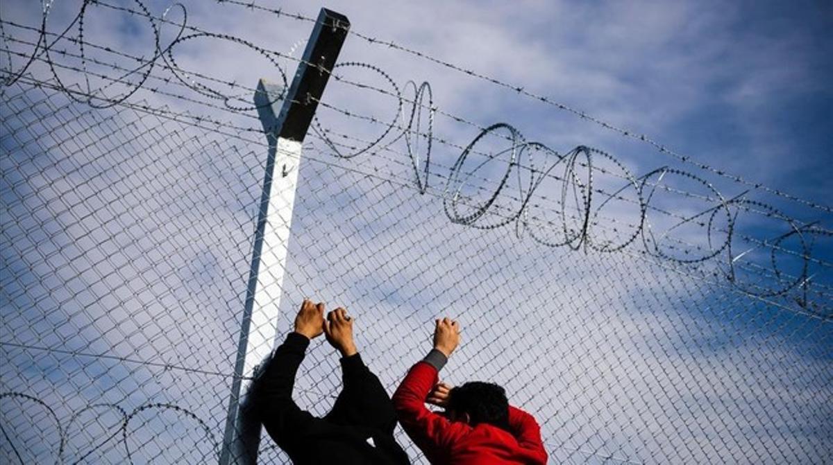 Dos refugiados en la frontera entre Grecia y Macedonia.