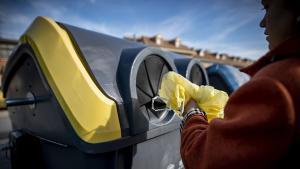 Una mujer deposita un envase de plástico en el contenedor amarillo.