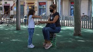 Una niña echa gel hidroalcohólico en las manos de su madre, en un parque de Barcelona, el pasado 6 de octubre.