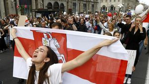 Una mujer con la antigua bandera nacional de Bielorrusia encabeza una marcha de protesta, este viernes en Minsk.