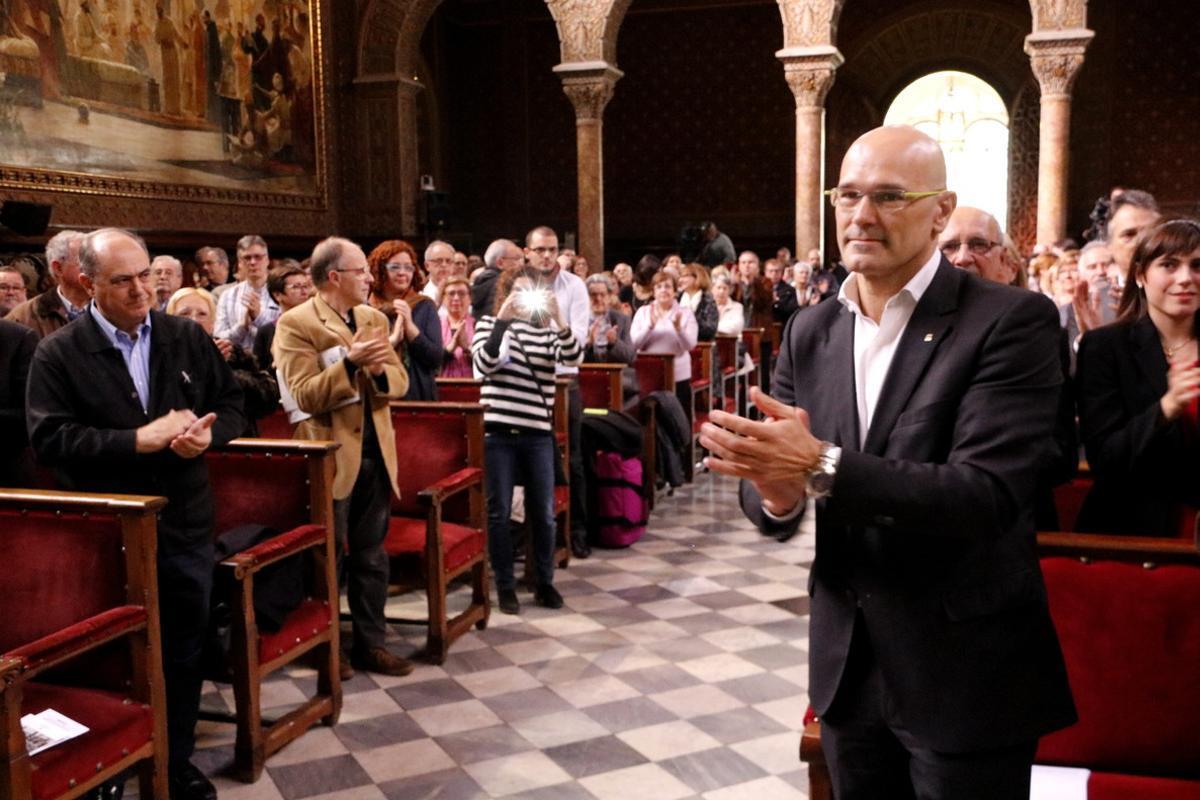 El 'conseller' Raül Romeva aplaude a los homenajeados en el acto de la Generalitat dedicado a los represaliados por la guerra civil y el franquismo, este domingo en el paraninfo de la UB.
