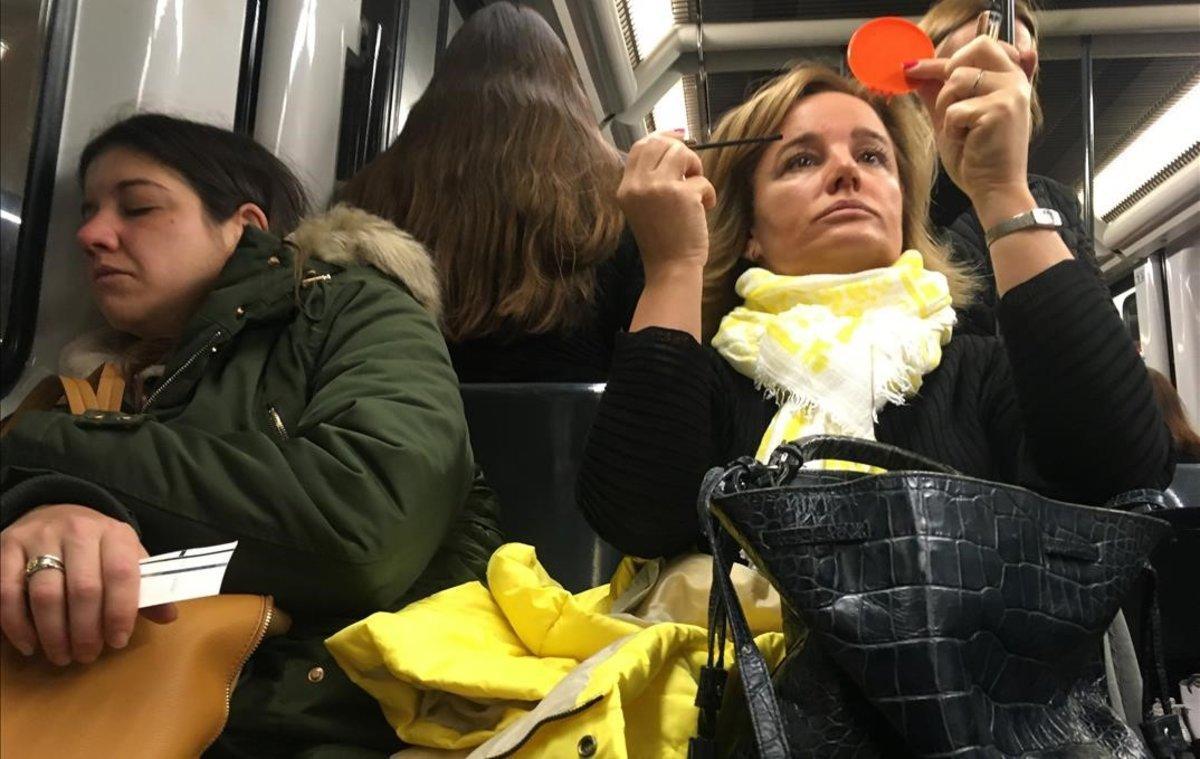 Una mujer se maquilla y otra duerme en un vagón del metro de Barcelona.