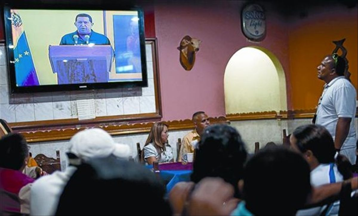 Clientes de un bar en Caracas siguen el discurso televisado de Chávez, ayer.
