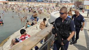Un policía fuertemente armado patrulla por la playa de Los Catalanes, en Marsella.