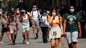 Paseantes con mascarilla por las calles del centro de Barcelona.
