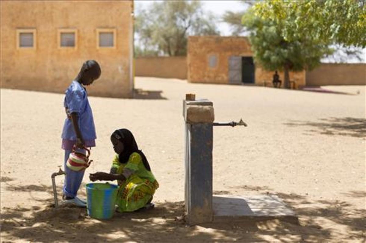Poblado en Mauritaniadonde Uniceflleva a cabo tareas de higiene, saneamiento y agua potable. En la imagen, dos alumnos se lavan las manos en el grifo del patio de la escuela.