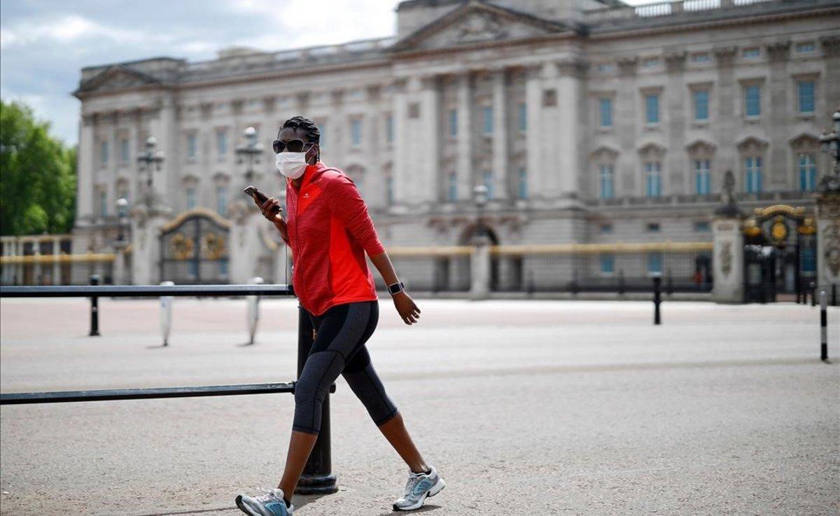 Un ciudadano pasa frente al palacio de Buckingham.