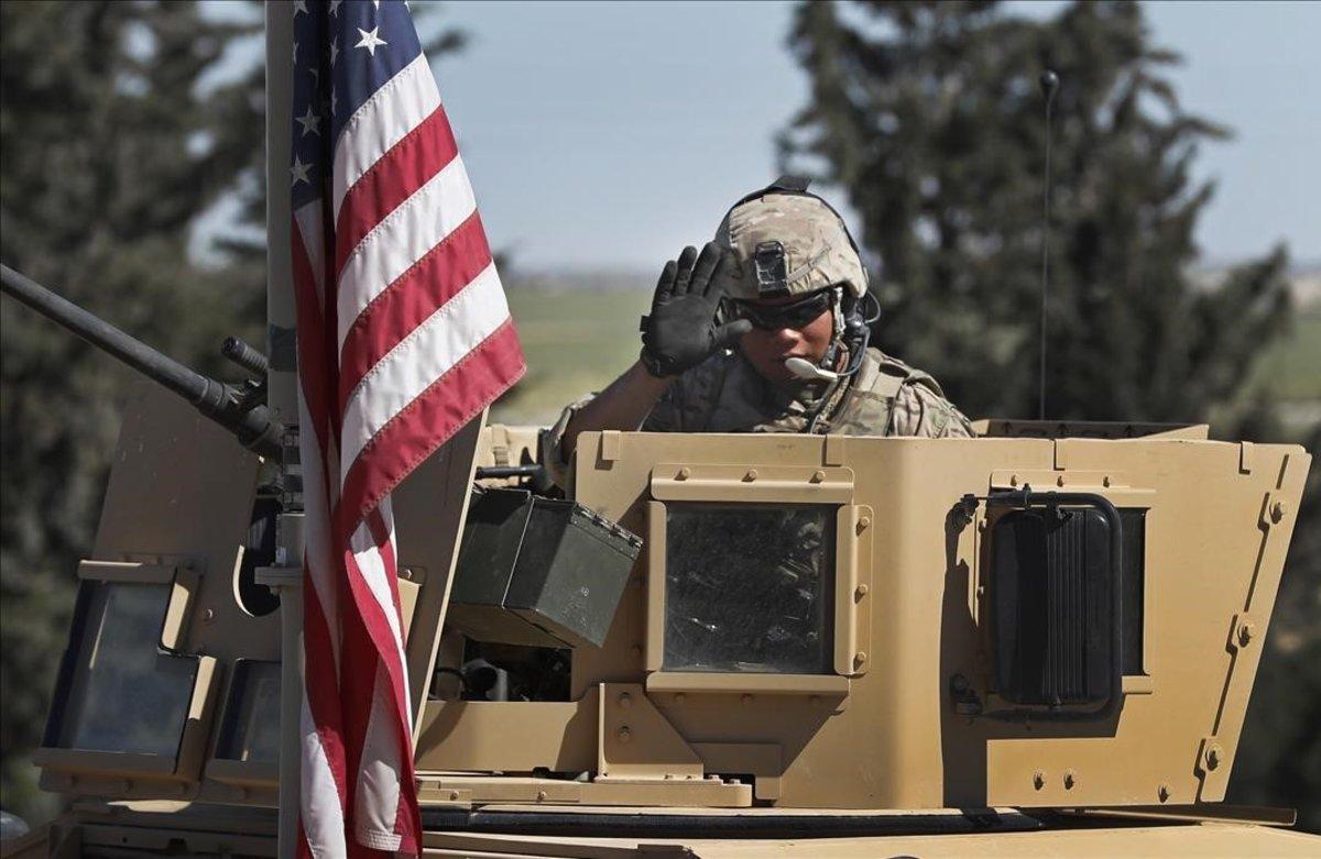 Un soldado de EEUU saluda desde un vehículo blindado en una carretera que conduce a la ciudad de Manbij, al norte de Siria.