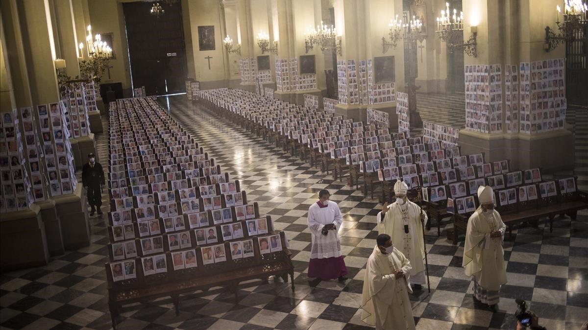 El arzobispo de Lima bendice a víctimas del covid-19, representados con fotografías en la catedral.