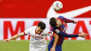 Munir y Piqué saltan a por el balón.