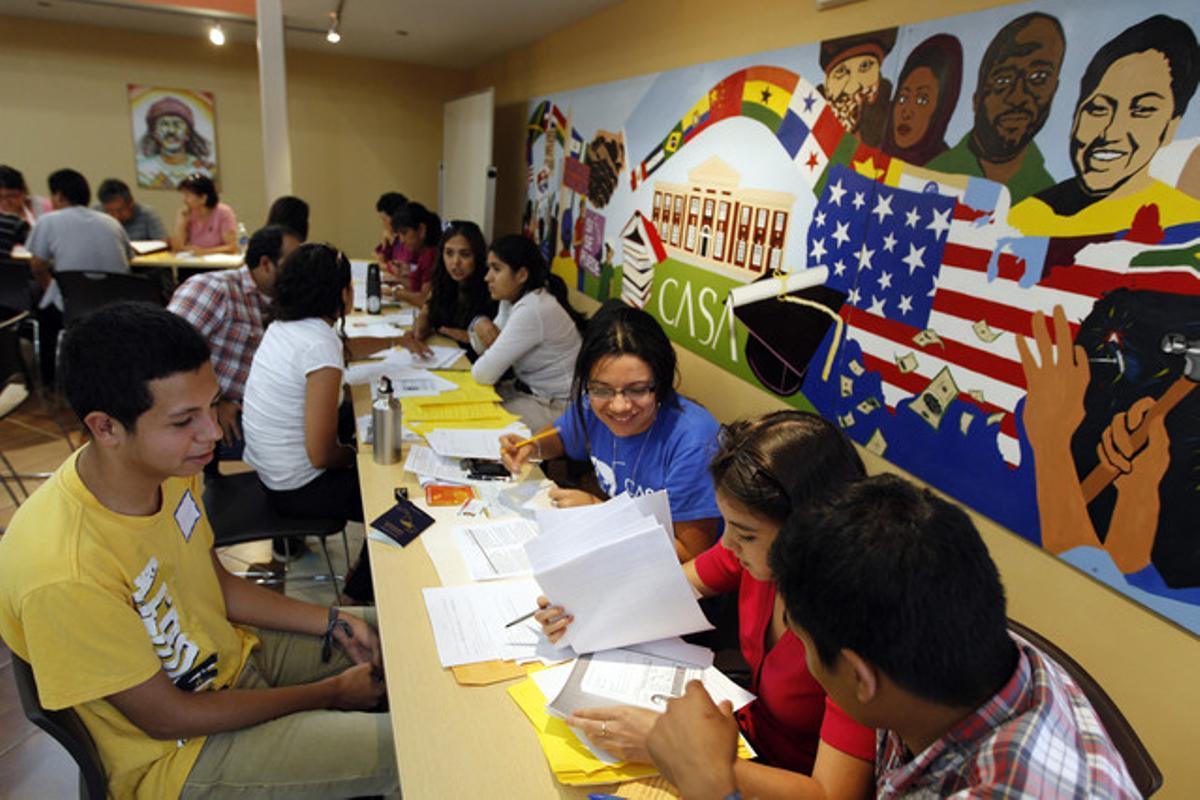 El joven Ángel Eduardo Aguiluz (izquierda), de origen hondureño, recibe información sobre cómo rellenar los formularios para regularizar su situación, el miércoles en Langley Park (Maryland).