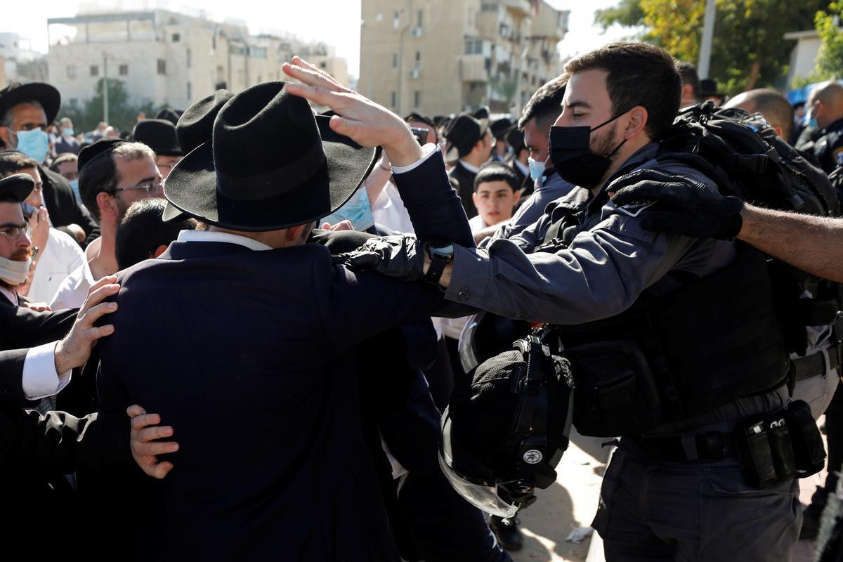 Un agente detiene a un ultraortodoxo en las manifestaciones contra las restricciones del covid.