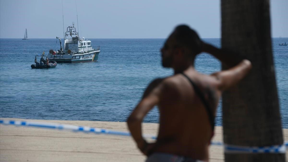 Sigue la expectación entre los bañistas para ver los trabajos de la Guardia Civil en la playa del Cristall en Badalona.