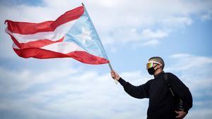 Bad Bunny ondea la bandera de Puerto Rico durante las protestas contra el gobernador Ricardo Roselló, en julio del 2019