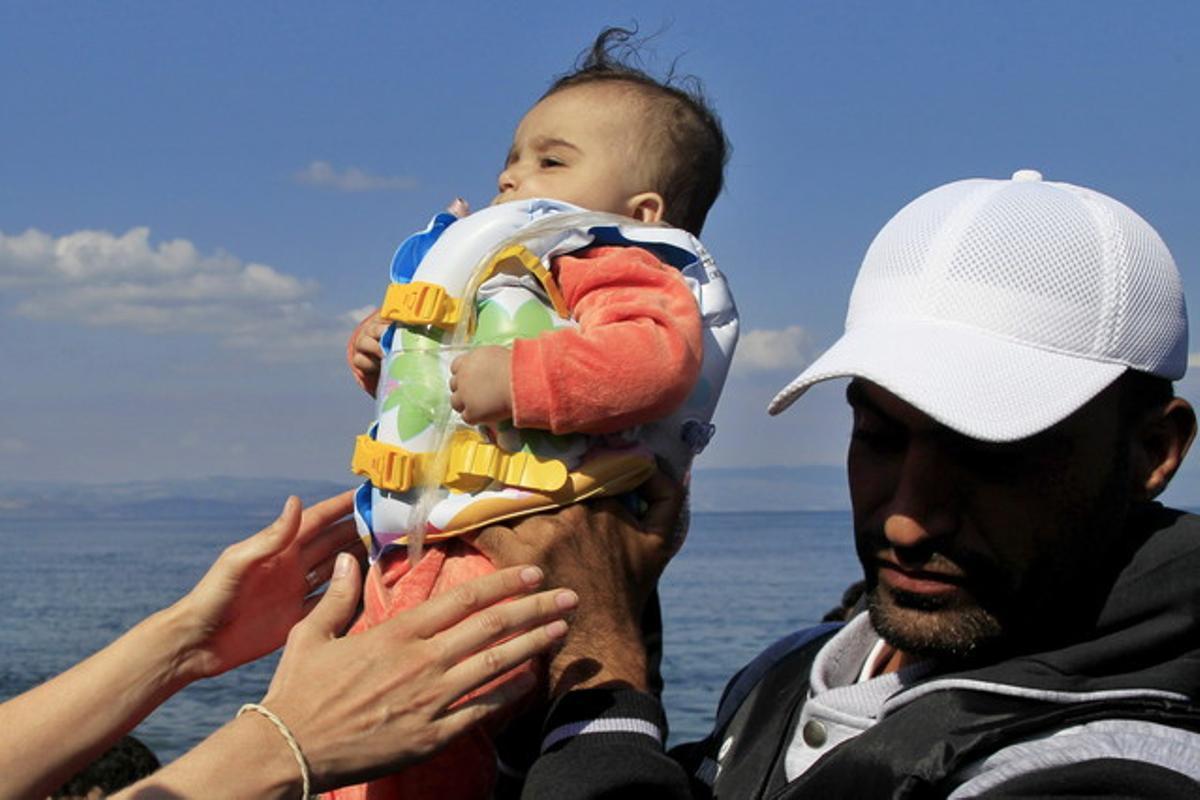 Un bebé llega a la isla griega de Mytilini tras salir de Turquía, este domingo.