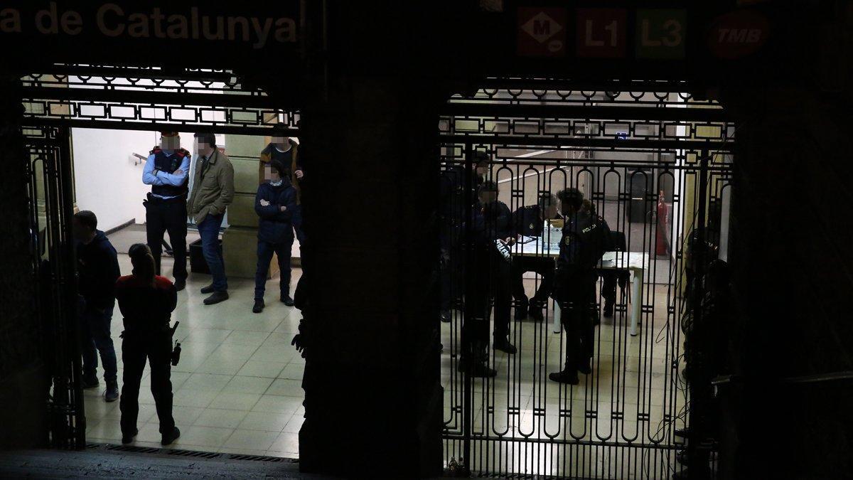 Varios policías en el subterráneo bajo las fuentes de la plaza de Catalunya, donde comprueban identidades de sospechosos.