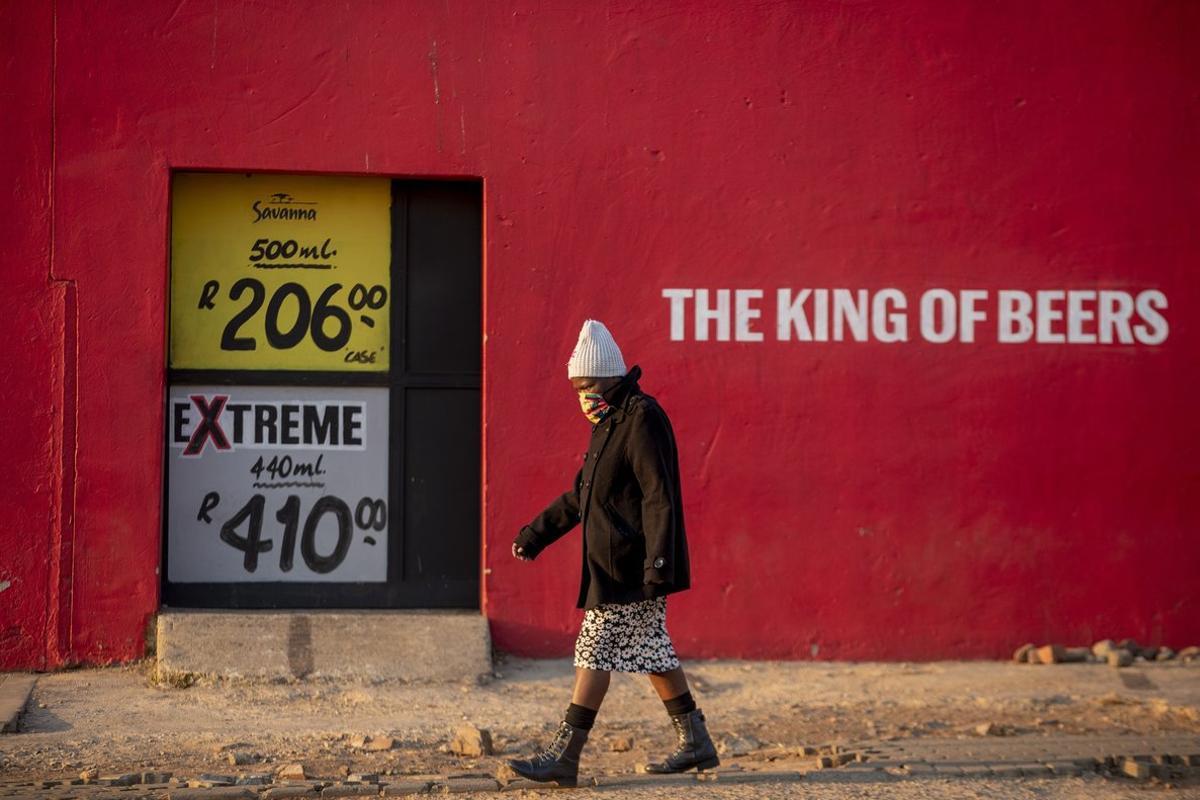 Una mujer pasa por delante de un comercio cerrado de venta de alcohol, en Soweto.