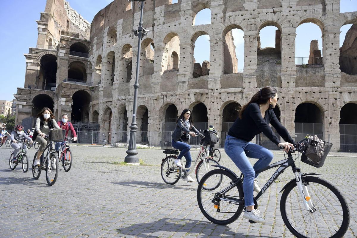 Unas chicas pasean en bicicleta por el Coliseo, en Roma.