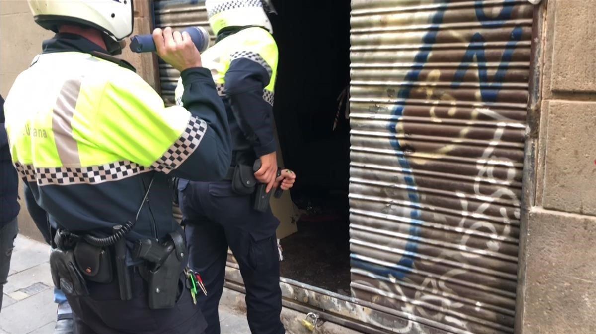 Dos agentes de la Guardia Urbana entran este martes pistola en mano en un narcopiso que no pudo ser clausurado durante la operación Bacar.