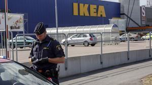 Un agente habla con unos clientes en las afueras del Ikea de Vasteras, en Suecia.
