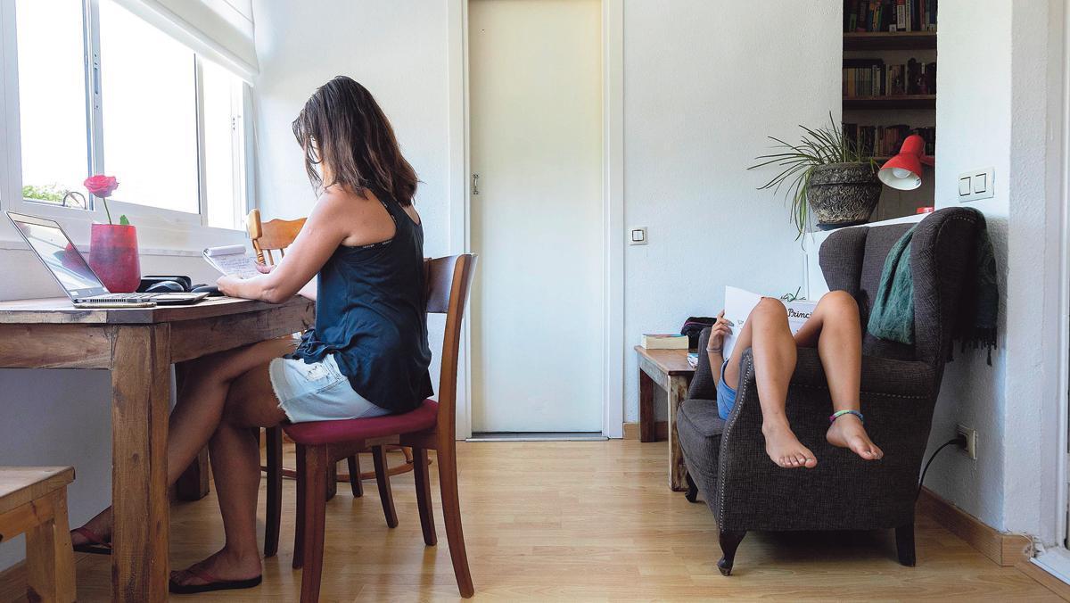 Una mujer teletrabaja en Barcelona debido a las restricciones por la pandemia de la covid-19, acompañada de su hijo.