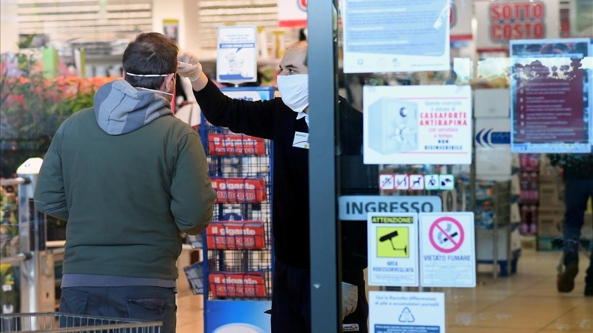 Un empleado de un supermercado toma la temperatura de un cliente a la entrada del establecimiento, el lunes en Milán.