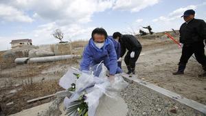 Un grup d'homes dipositen flors a Namie, a la prefectura de Fukushima.