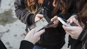 Unas jóvenes de Barcelona usan su móvil.