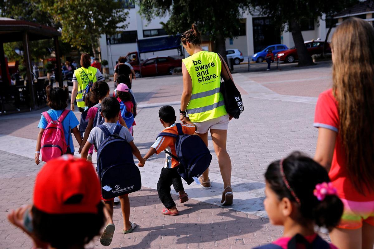 Unos voluntarios acompañan a la escuela a niños refugiados en la isla griega de Chios.