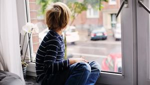 Un niño de siete años mira por la ventana de su casa, en una imagen de recurso.