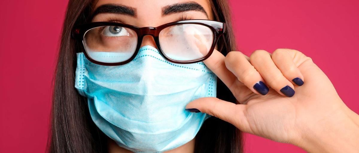 Mujer limpiándose las gafas tras la mascarilla