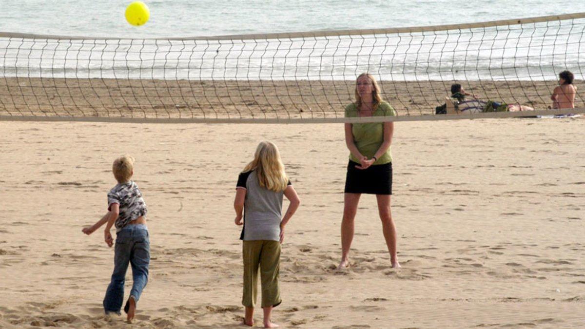 Una madre juega con sus hijos en una playa de Barcelona.
