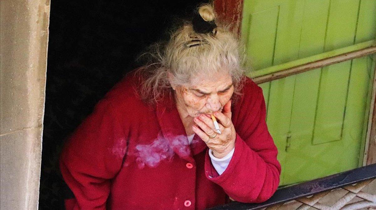 Una señora sale a fumar a su balcón, en una imagen captada por Joel Codina, en el Raval.