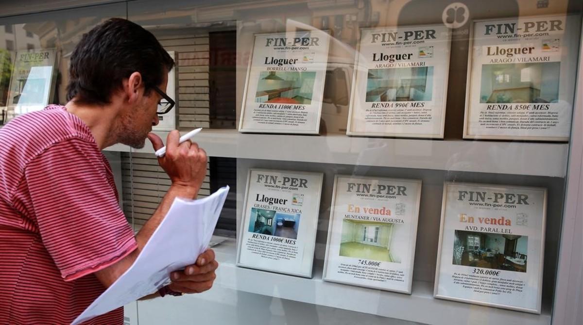 Un hombre busca piso en una agencia inmobiliaria del Poble Sec.